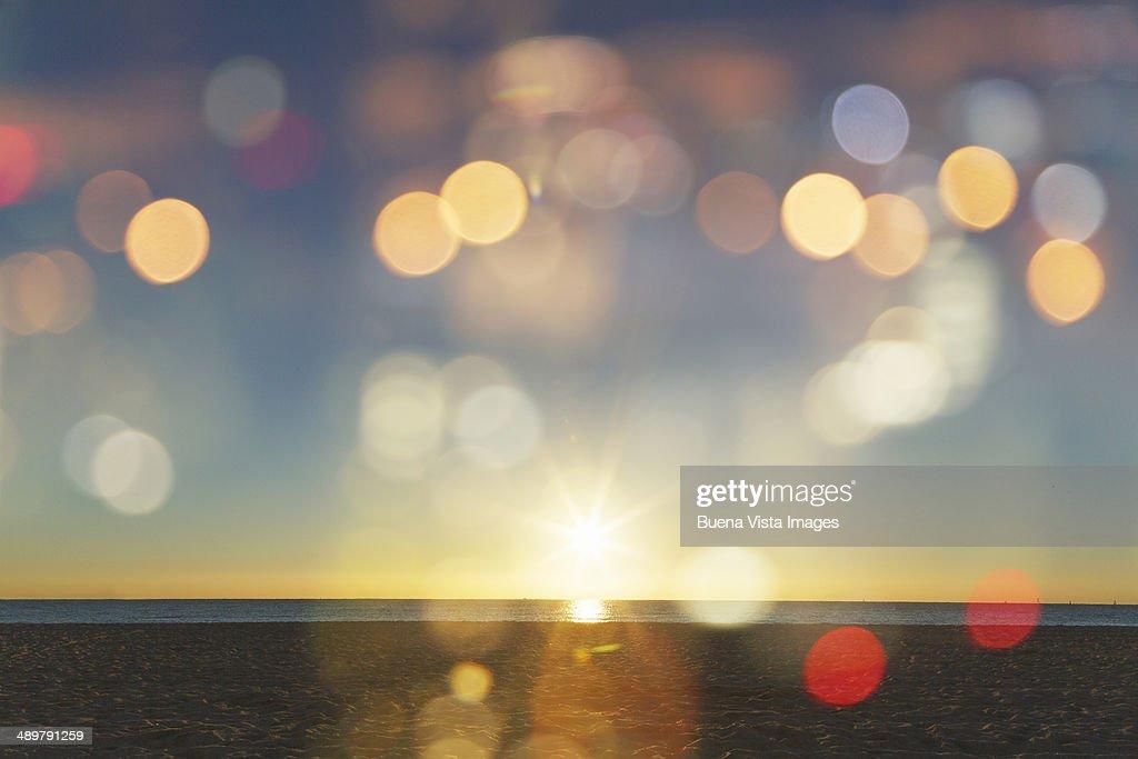Sunrise with lens flares over a beach : Stock Photo
