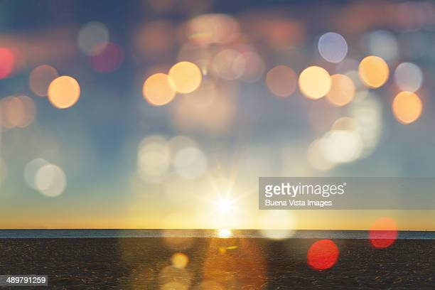 sunrise with lens flares over a beach - blendenfleck stock-fotos und bilder