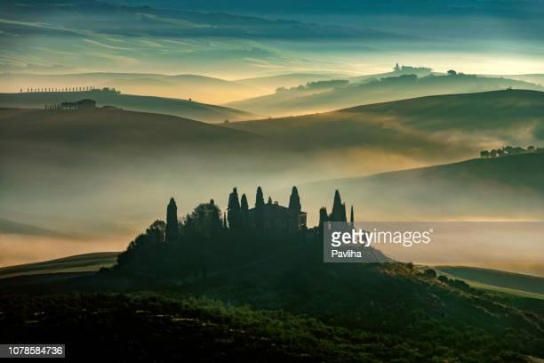zonsopgang met stralen over de mistige valleien in toscane, italië, europa - toscane stockfoto's en -beelden
