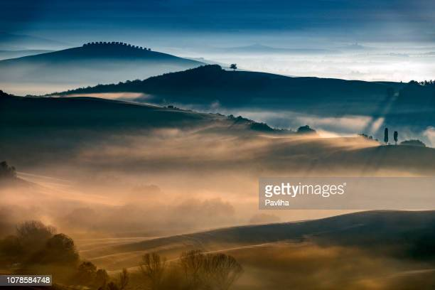 sunrise with rays over the misty valleys in tuscany,italy,europe - toscana foto e immagini stock