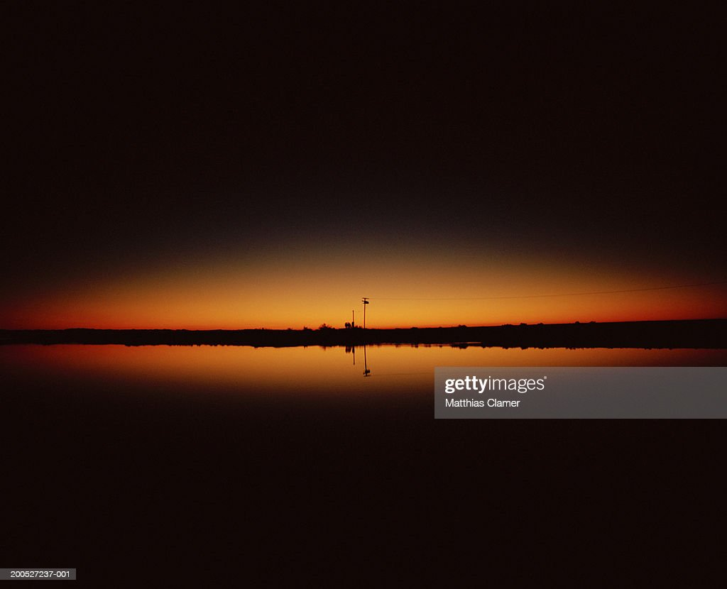 Sunrise with reflection in water on horizon : Stock Photo