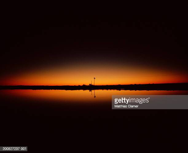 Sunrise with reflection in water on horizon