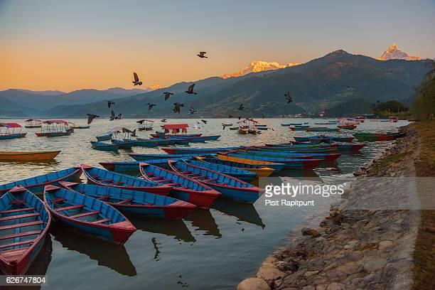 sunrise with wooden boats on phewa lake, pokhara, nepal. - pokhara stock pictures, royalty-free photos & images
