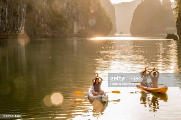 sunrise yoga and meditation in kayaks, lan ha bay, vietnam - halong bay stock pictures, royalty-free photos & images
