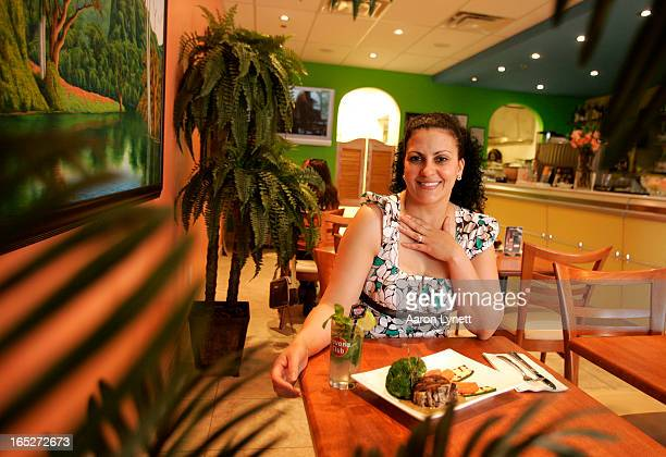 Aracelys Figuerevo owner of Havana Sunrise Cafe in Woodbridge displays a traditional Cuban dish Fileton Criollo in Havana Sauce and a a Mojito