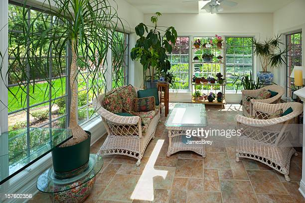 Sunroom Greenhouse Interior With Casual Wicker Furniture, Plants, Tile Floor