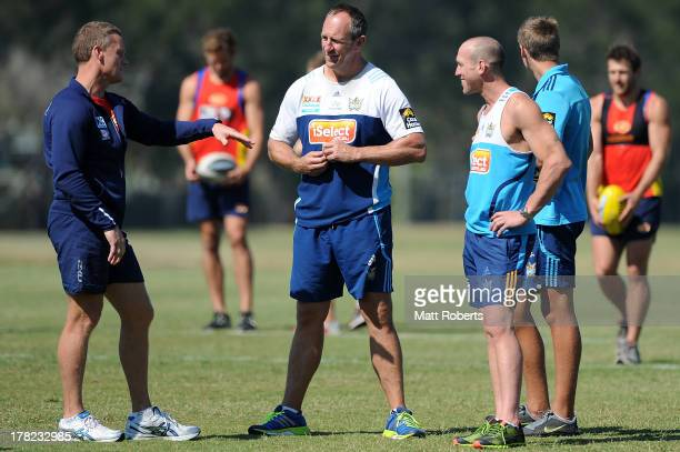 Suns coach Guy McKenna speaks with Titans coach John Cartwright during a Gold Coast Titans training session at Metricon Stadium on August 28 2013 on...
