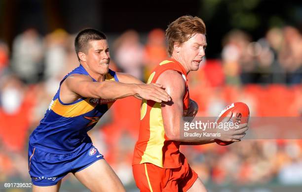 Suns player Jesse Joyce is pressured by the defence of West Coast Eagles player Liam Duggan during the round 11 AFL match between the Gold Coast Suns...