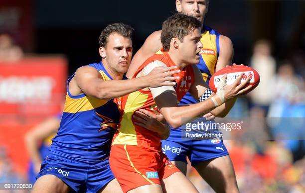 Suns player Kade Kolodjashnij is pressured by the defence during the round 11 AFL match between the Gold Coast Suns and the West Coast Eagles at...