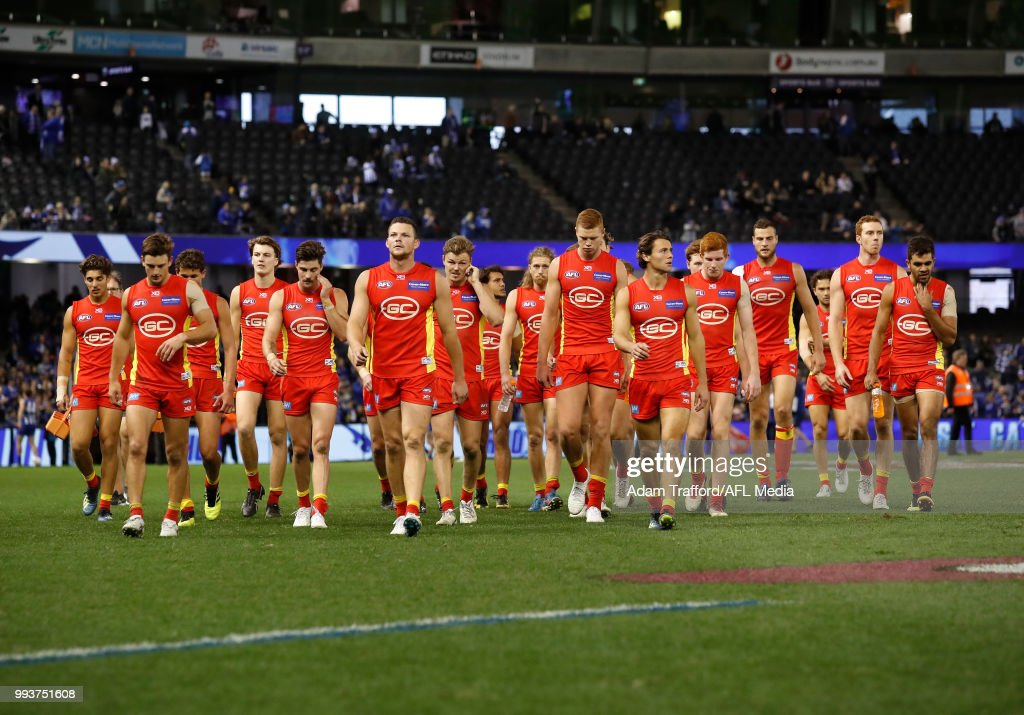 Suns players look dejected after a loss during the 2018 AFL round 16 match between the North Melbourne Kangaroos and the Gold Coast Suns at Etihad Stadium on July 08, 2018 in Melbourne, Australia.
