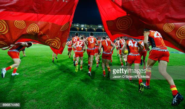 Suns players take the field during the round 13 AFL match between the Gold Coast Suns and the Carlton Blues at Metricon Stadium on June 17 2017 in...