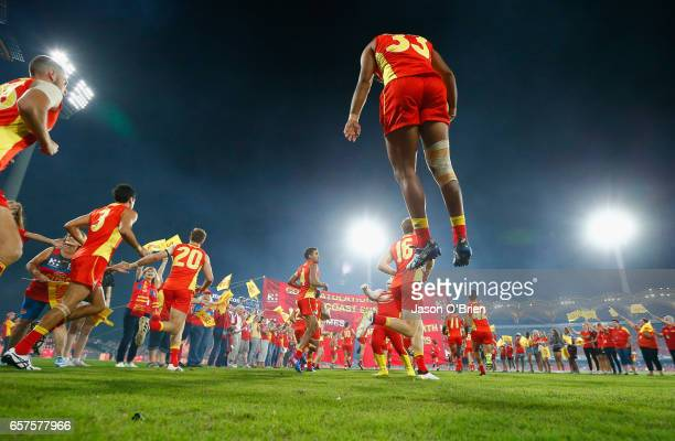 Suns players take the field during the round one AFL match between the Gold Coast Suns and the Brisbane Lions at Metricon Stadium on March 25 2017 in...