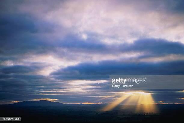 sun's rays shining through storm clouds over rural landscape - penetracion fotografías e imágenes de stock