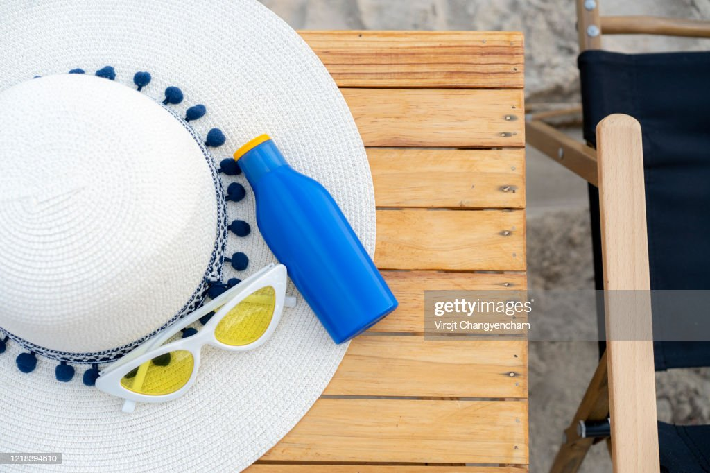 Sunscreen, weave hat and sunglass on wooden table : Stock Photo