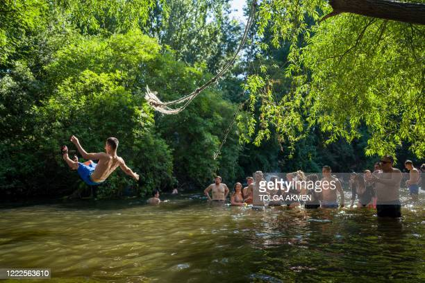 Sun-seekers cool off in the water and sunbathe on the riverbank at Hackney Marshes in east London on June 24 as temperatures reached 31 degrees C at...