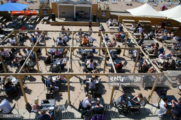 Sun-seekers enjoy warm sunny weather in the beer garden on the Brighton seafront.