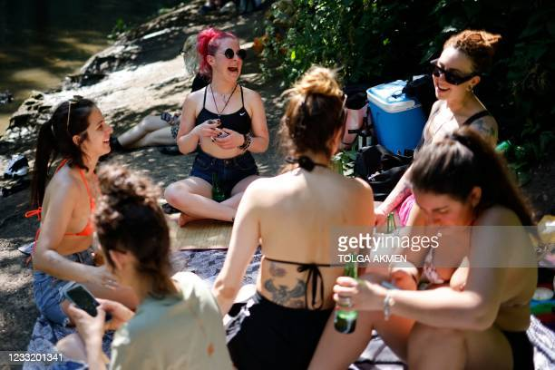 Sun-seekers play cards on the riverbank at Hackney Marshes in east London on May 31 as fine and dry conditions continue in the UK on what could be...