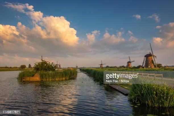 sunset above old windmills in kinderdijk - キンデルダイク ストックフォトと画像