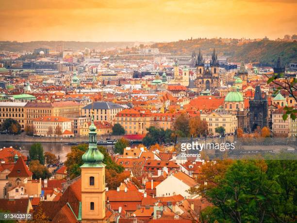 sunset aerial top view of red roofs in the city of prague, czech republic from prague castle during autumn - notre dame de tyn photos et images de collection