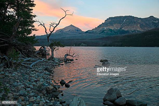 Sunset along the shoreline of Saint Mary Lake with Triple Divide Peak on the horizon in Glacier National Park Montana on a summer evening Saint Mary...