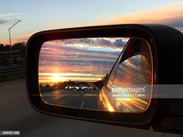 sunset and cars reflecting in side view mirror - side view mirror stock photos and pictures