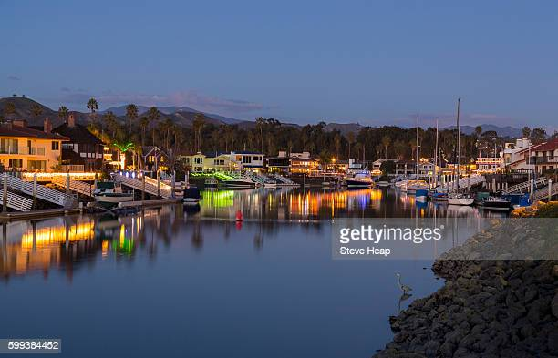 Sunset and dusk at residential development of modern homes and boats by water with Christmas lights in Ventura, California, USA