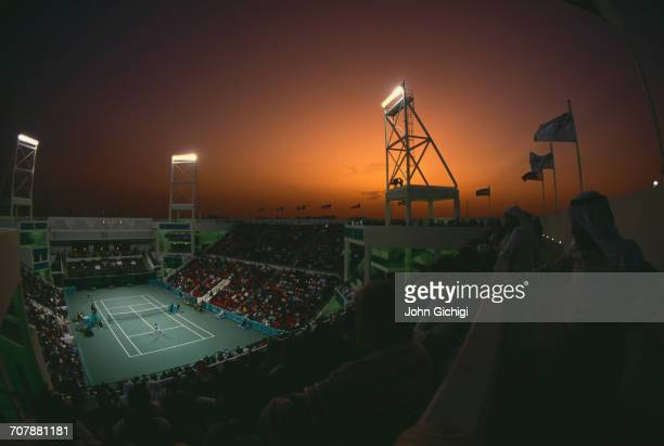 Sunset and floodlights illuminate the spectators watching a Men's singles match on the centre court during the Mannai Cadillac Qatar Tennis Open on...