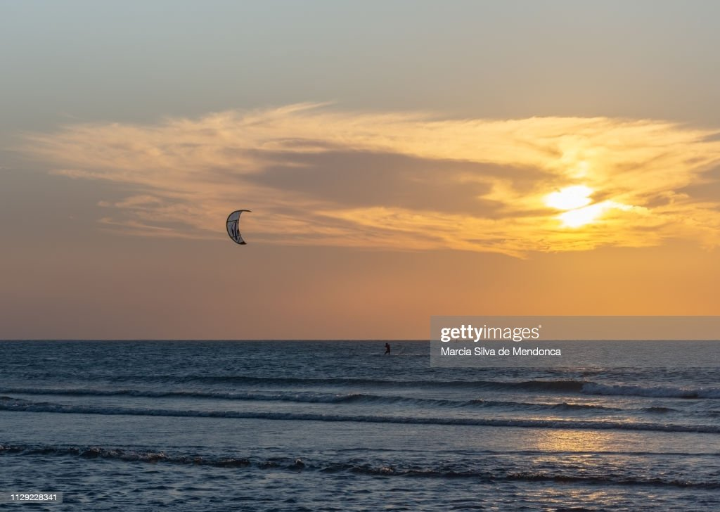 Sunset and kitesurfing practice at Jericoacoara beach. : Stock Photo