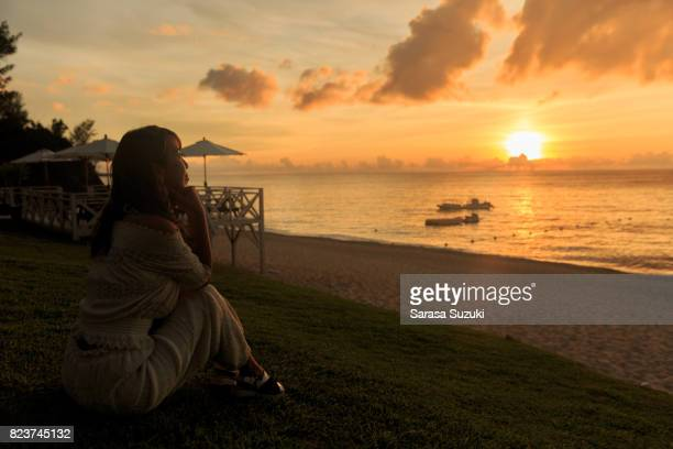 sunset and ladies. - waimea bay hawaii stock photos and pictures