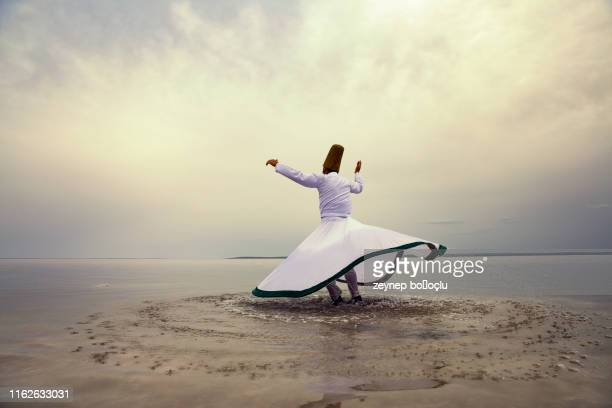 sunset and whirling at the sea, sufi. sufi whirling (turkish: semazen) is a form of sama or physically active meditation which originated among sufis. - east stock pictures, royalty-free photos & images