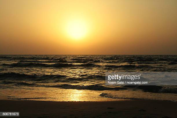 sunset at a beach - noam galai stock pictures, royalty-free photos & images