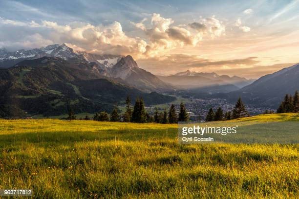 sunset at a mountain pasture over garmisch-partenkirchen - sonnig stock-fotos und bilder