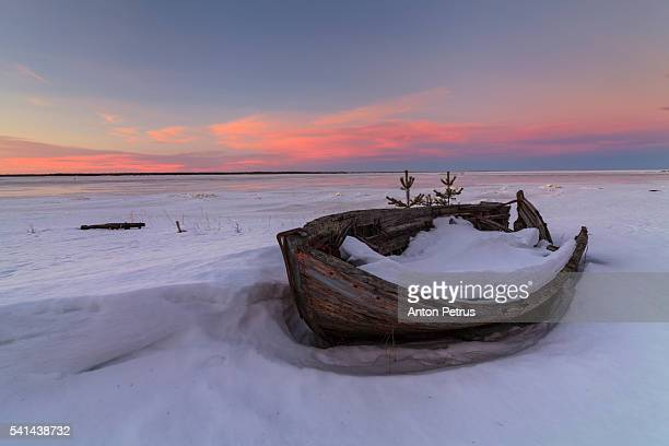 Sunset at an old boat in the winter