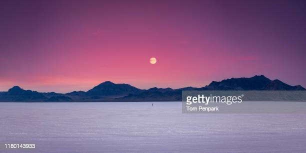 sunset at bonneville salt flats with unrecognized woman running in distance, wendover, utah, usa - bonneville salt flats stock pictures, royalty-free photos & images