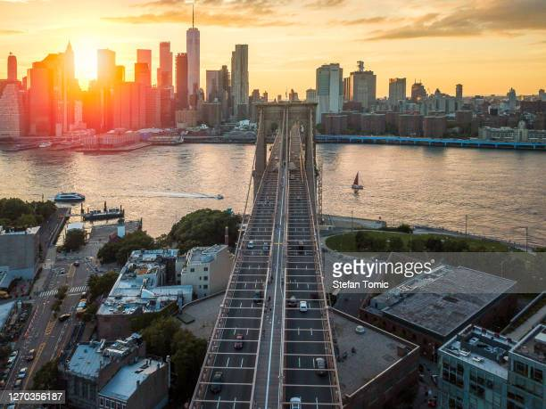 sunset at brooklyn bridge overlooking downtown manhattan - brooklyn bridge stock pictures, royalty-free photos & images