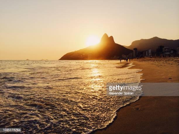 sunset at ipanema beach, rio de janeiro, brazil - copacabana rio de janeiro stock-fotos und bilder