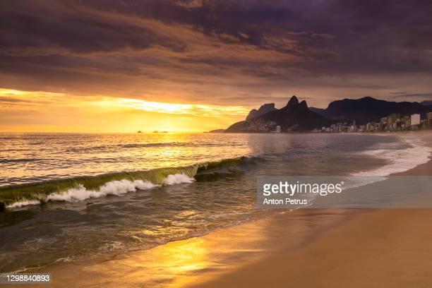 sunset at ipanema beach with storm waves, rio de janeiro, brazil - rio de janeiro stock pictures, royalty-free photos & images