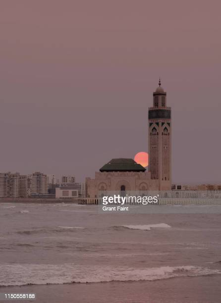sunset at mosque - mosque hassan ii stock photos and pictures