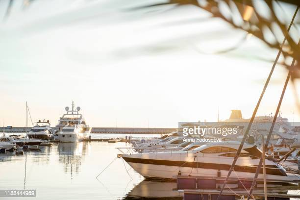 sunset at sea. berth with yachts. a seaport lit by the setting rays of the sun. calm expanse of water and ships. sun glare. - moored stock pictures, royalty-free photos & images