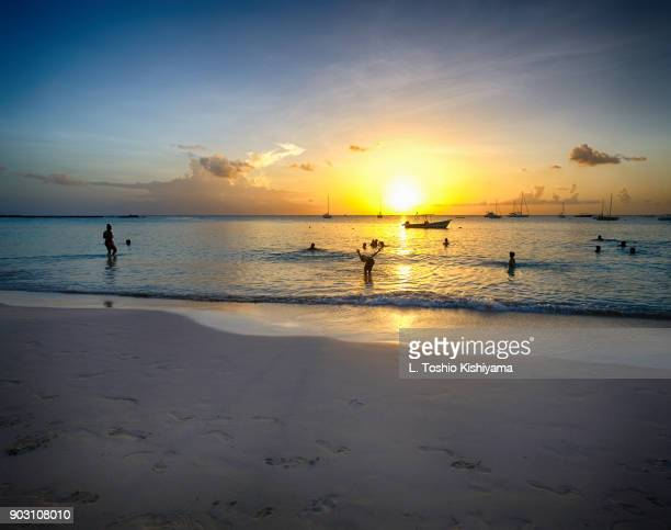 sunset at the beach in barbados - bridgetown barbados stock photos and pictures