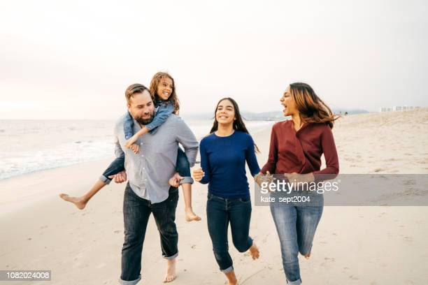 sunset at the beach with family - mixed race person stock pictures, royalty-free photos & images