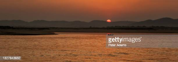 sunset at the irrawaddy river in bagan, myanmar - peter adams stock pictures, royalty-free photos & images