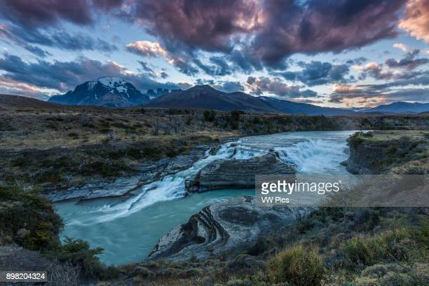 Sunset at the Rio Paine Waterfalls Torres del Paine National Park Chile In the distance are Monte Almirante Nieto the three Torres del Paine and...