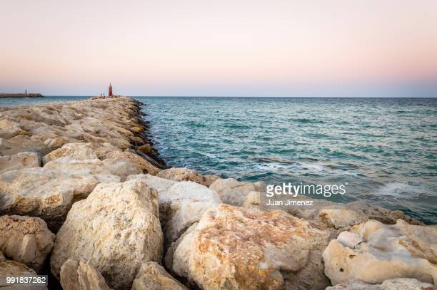 sunset at the seawall - seawall stock pictures, royalty-free photos & images