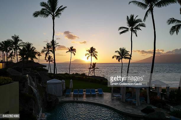 Sunset at Wailea Beach as viewed from the Four Seasons Resort Maui at Wailea palm trees and pool visible Wailea Maui Hawaii 2016