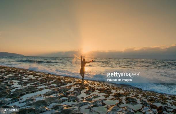Sunset Beach Hawaii Oahu North Shore fisherman throwing net for fish in rocky shore for bait in sunset