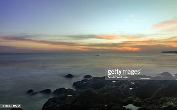 sunset beach paradise in bali - made widhana stock photos and pictures