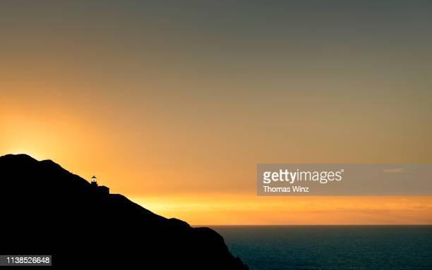 sunset behind a lighthouse - betrouwbaar stockfoto's en -beelden
