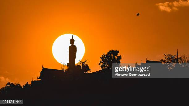 sunset behind buddha state of wat phra that doi kham, buddhist temple in the historic of chiang mai, thailand. - buddha state stock pictures, royalty-free photos & images