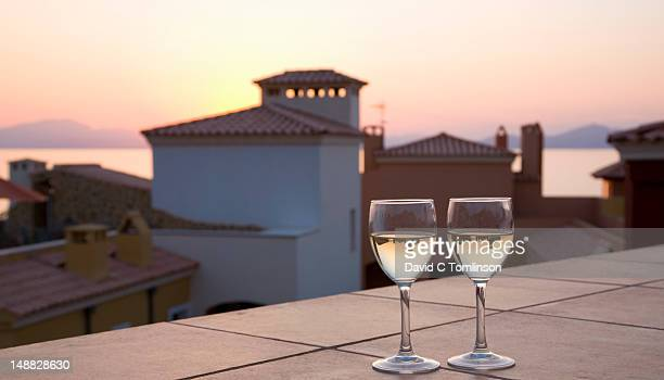 Sunset behind modern apartment buildings overlooking the Badia dÆAlcudia at Betlem, near Colonia de Sant Pere, with two glasses of wine in foreground.